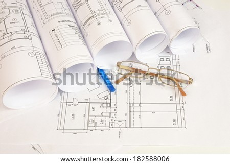 Construction drawings, glasses and pen on wooden surface. Workplace architect - stock photo