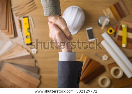Construction engineer and businessman shaking hands top view close up, desktop with work tools and wood swatches on background - stock photo