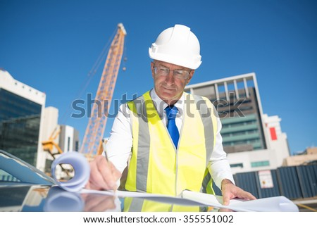 Construction engineer in hardhat making notes in blueprint - stock photo