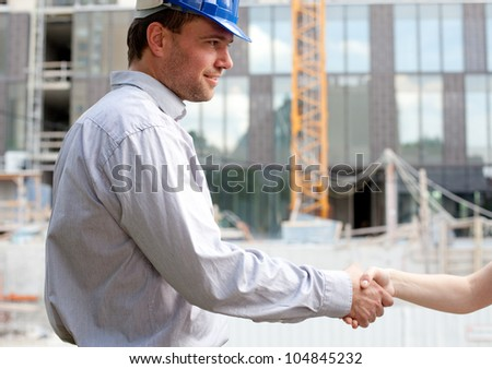 Construction engineer shaking hands at construction site - stock photo