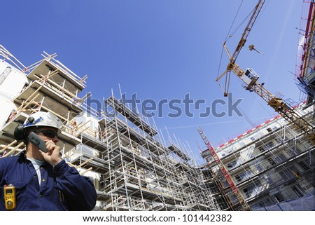 construction engineer with large scaffolding in background, wide angle perspective - stock photo