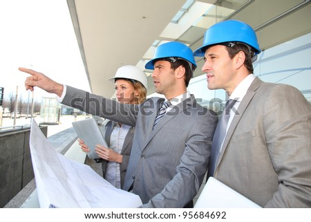 Construction engineers checking building site - stock photo