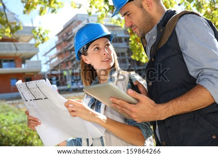 Construction engineers working together on site - stock photo