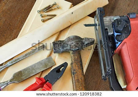 Construction equipment. Electric a jigsaw, pliers and wood chisels lying on the wooden planks.