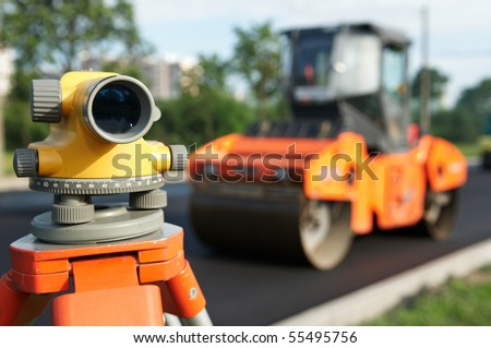 Construction equipment theodolite level tool at asphalt pavement works in summer - stock photo