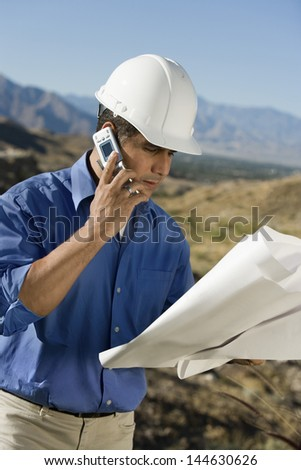 Construction foreman in hardhat using mobile phone while looking at blue print on site - stock photo