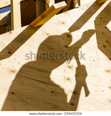 Construction framing contractor carpenter building out the gable end of the roof with purlin and facia trim boards - stock photo