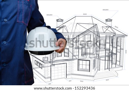 Construction hard hat in hand. House model