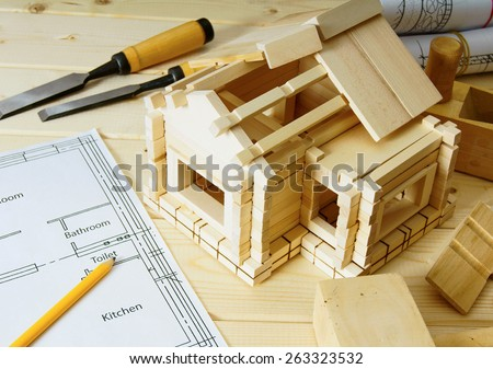 Construction house. Joiner's works. Drawings for building, small wooden house and working tools on wooden background. - stock photo