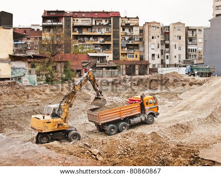 construction machine excavating earth into a truck - stock photo