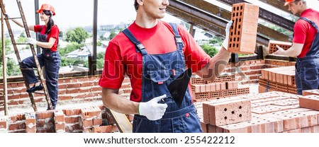 construction man mason worker bricklayer installing red brick with trowel putty knife outdoors and full length body woman on metal stairway stand on roof house against summer city town street - stock photo