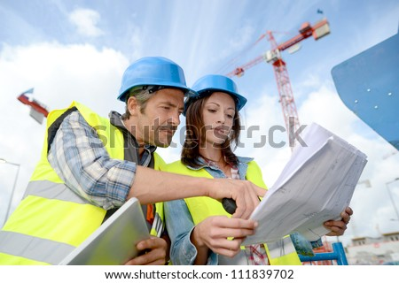 Construction manager and engineer working on building site - stock photo