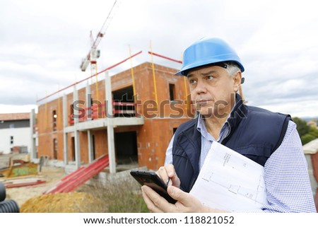 Construction manager on building site using smartphone - stock photo