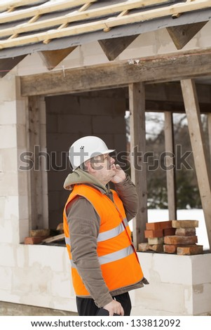 Construction manager  talking on the cell phone near new building - stock photo