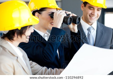 construction manager viewing construction site with binoculars - stock photo