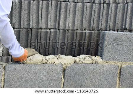 construction mason worker bricklayer installing  brick with trowel putty knife outdoors - stock photo
