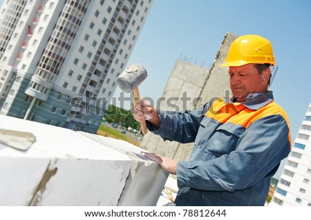 construction mason worker bricklayer installing calcium silicate brick by hammer hitting work - stock photo