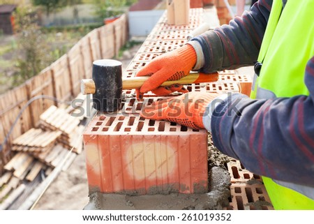 Construction mason worker bricklayer installing red brick with rubber mallet outdoors - stock photo