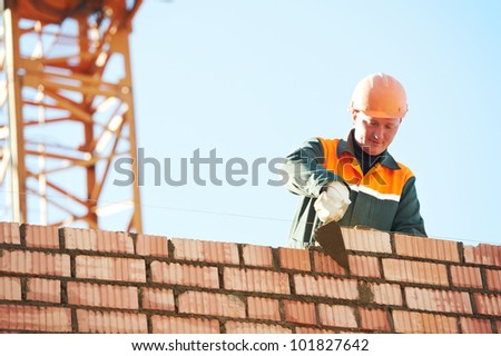 construction mason worker bricklayer installing red brick with trowel putty knife outdoors - stock photo
