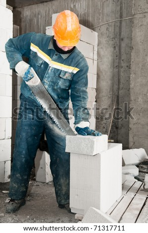 construction mason worker bricklayer sawing off a lime sand brick - stock photo