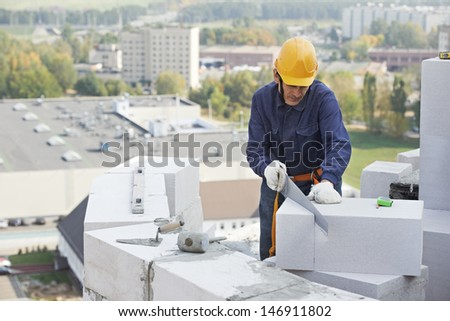 construction mason worker bricklayer working with limestone brick with trowel putty knife outdoors - stock photo