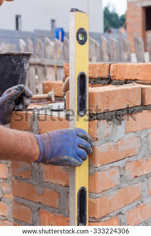 Construction mason worker measuring with professional level the bricks on walls - stock photo