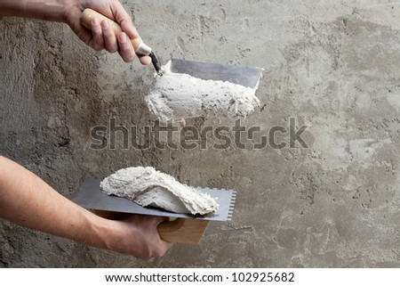 construction notched trowel and worker hands with white mortar on wall - stock photo