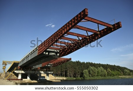 Construction of a bridge over the reservoir. Installation of metal bridge spans.