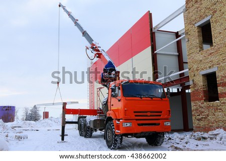 Construction of a modern sport complex with a universal truck manipulator crane in the winter - stock photo