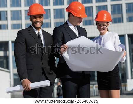 Construction of a new business center. Three confident business architect in protective helmet standing on the site and view the object holding blueprints in hand. Business team. Architects concept.