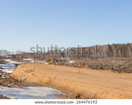 Construction of a new road between the settlements, and sand mound marked with wooden pegs for leveling height in early spring - stock photo
