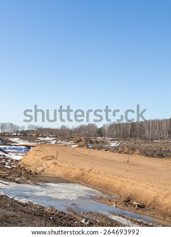 Construction of a new road between the settlements, and sand mound marked with wooden pegs for leveling height in early spring, vertically - stock photo