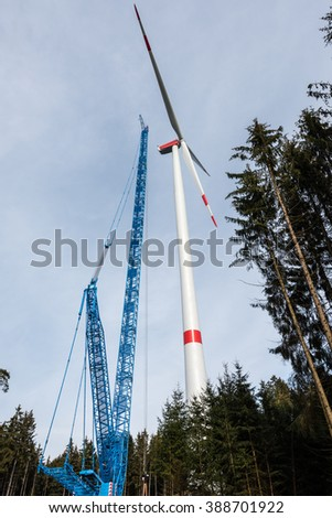 Construction of a wind turbine with large crane in wood glade - stock photo