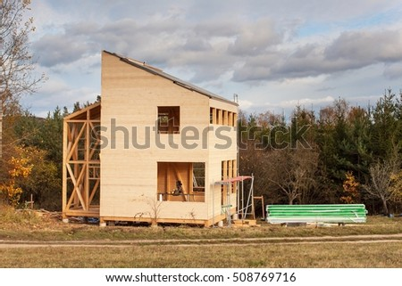 Construction of ecological house. External work on the building envelope. The wooden structure of the house near the forest.