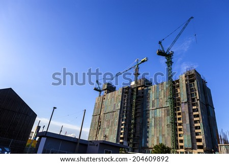 construction of high-rise building by tower cranes and the canvas to protect the dust on blue sky background - stock photo