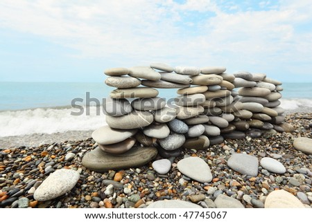 construction of many pebbles on a sea coast near water. focus on left part of construction. - stock photo