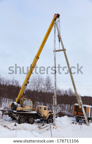 Construction of power lines using a mobile crane in a winter snowy forest