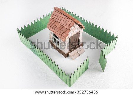 Construction of toy brick house with green fence. White background. Top perspective view. - stock photo