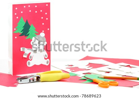 Construction paper, bag, stencils, pencil and scissors to make Christmas gift bags