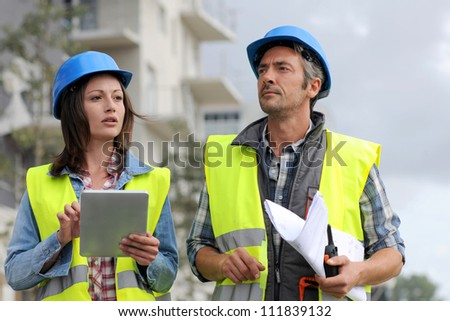 Construction people walking on building site - stock photo