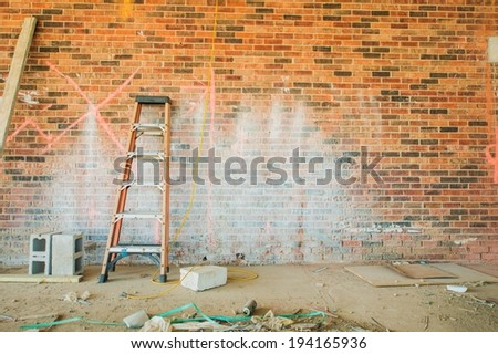 Construction Place with Small Ladder and Dirty Brick Wall.