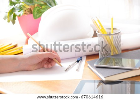 Construction plans in hand with helmet, measure, mobile phone, and drawing tools