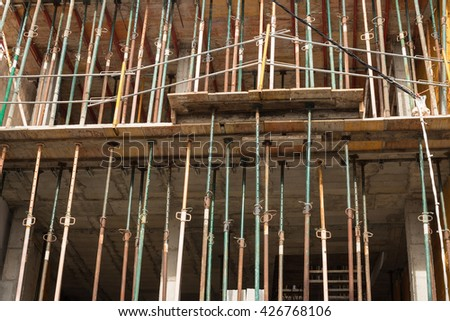 Construction props supporting an unfinished concrete structure - stock photo
