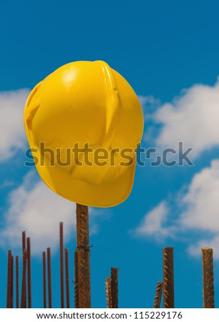 Construction protective helmet left hanging from reinforcement steel bars - stock photo