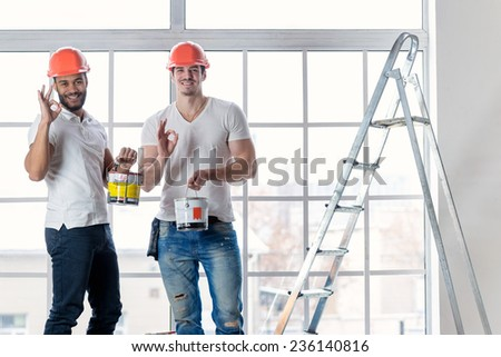 Construction, repair and moving into an apartment. Two workers wearing helmets keep the paint and make repairs in a new apartment ladder while standing in an empty apartment and show Okay - stock photo