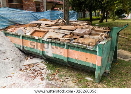 Construction rubbish bin with loads at construction site. - stock photo