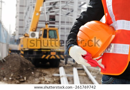 Construction safety concept, close-up worker wearing safety vest holding helmet with crane in the background - stock photo