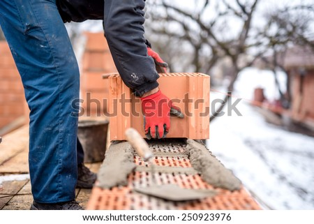 construction site and mason bricklayer working with bricks, cement and mortar for building new house - stock photo