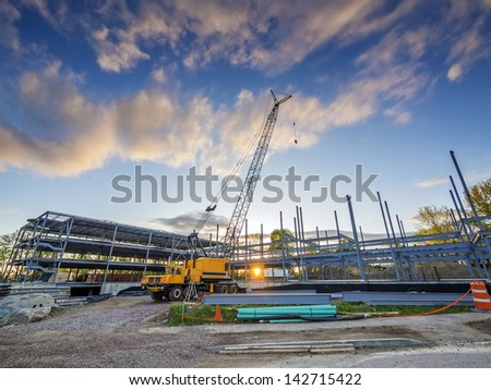 Construction site at sunset with crane and building
