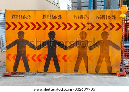 Construction site border with warning signs and text on Italian means post no bills posting - stock photo